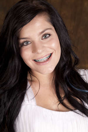 braces: A close up of a teen girl with a happy expression on her face.