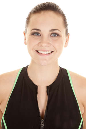 A close up of a woman smiling in her zip up exercise top.