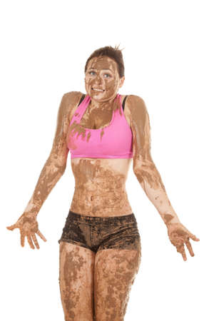 A woman covered in mud with a funny expression on her lips. photo