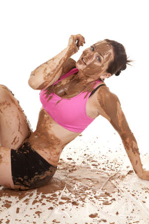 A woman sitting in a pile of mud with it all over her body. photo