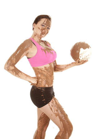 A woman covered in mud holding on to her volleyball covered in mud. photo