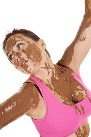 A woman covered in mud with a serious expression on her face. photo