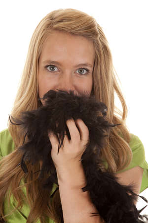 A teen girl with a black feathered boa over her mouth showing expression with her eyes. photo