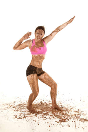 A woman covered in mud striking a pose.