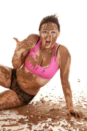 A woman with a shocked expression on her face with mud all over her body. photo