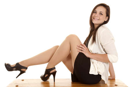A woman sitting on a bench in her business clothes with a smile on her face Stock Photo
