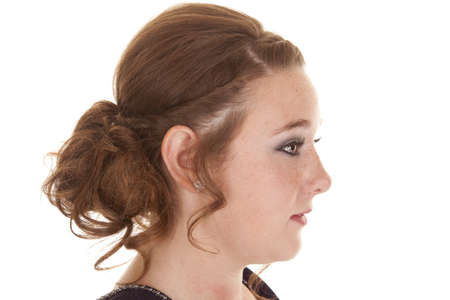 A side view of a teen girl with her hair done fancy. photo