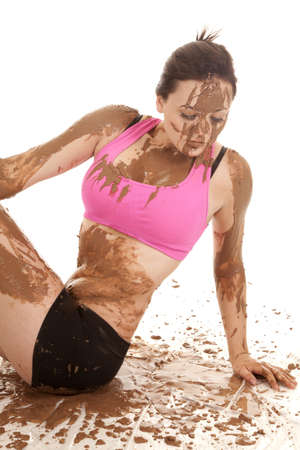 A woman sitting in mud looking down. photo