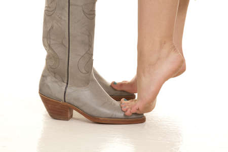 barefoot cowboy: A woman standing on the toes of her mans cowboy boots.