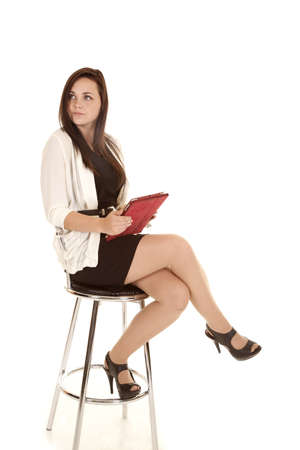 a woman sitting on a stool holding her pad in her hand looking away.