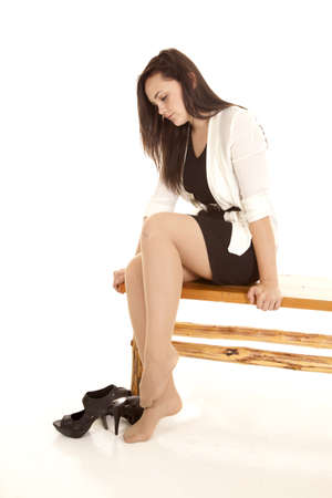 A woman sitting on a bench resting her feet by taking off her shoes.