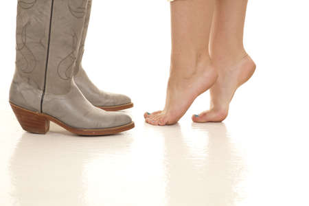 bare body women: a woman standing on her tip toes to reach her mans lips while he is in his cowboy boots.