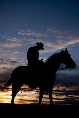 A cowboy is asleep on his horse in the sunset. Stock Photo