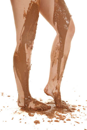 A womans legs covered in mud with it running down her legs. photo