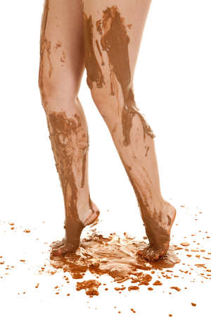 A womans legs dripping with mud down her leg and off her toes photo
