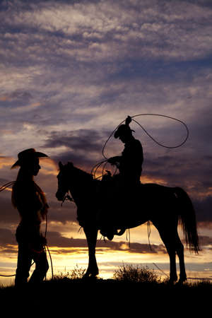 A cowboy is sitting on a horse in the sunset swinging a rope with the silhouette of a cowgirl standing off to his side holding on to her rope. photo