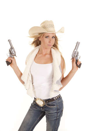 A cowgirl showing her power by holding up her two pistols and aiming them to the sky.