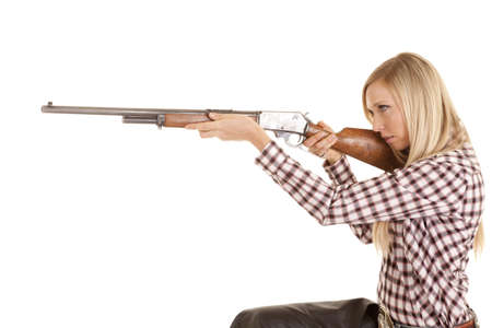 a cowgirl sitting down and aiming her rifle. Stock Photo