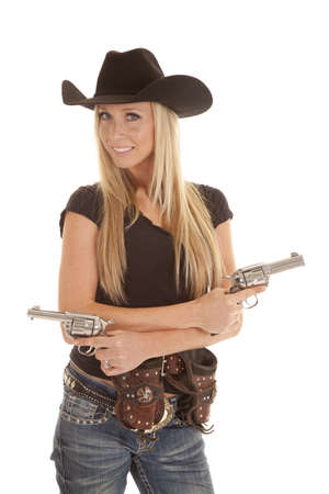 A cowgirl standing with her pistols in her hands and her holsters on her hips. photo