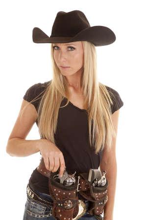 A cowgirl placing one of her pistols in her holster with a serious expression on her face. photo