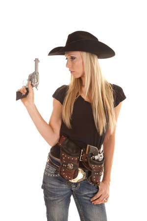 holster: a cowgirl dressed in black holding up her pistol with her other gun in her holster. Stock Photo