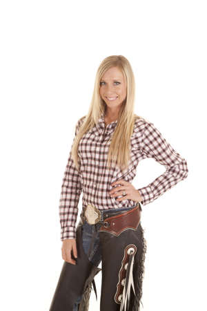 plaid shirt: A cowgirl in her plaid shirt and chaps with  a smile on her face.