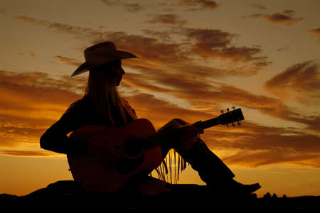 A cowgirl sitting on the ground playing her guitar with a beautiful sunset in the background.