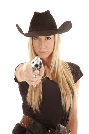 A cowgirl pointing her pistol at the camera with a serious expression on her face. photo