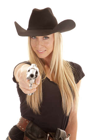 A cowgirl pointing her pistol at the camera with a smile  on her face. photo