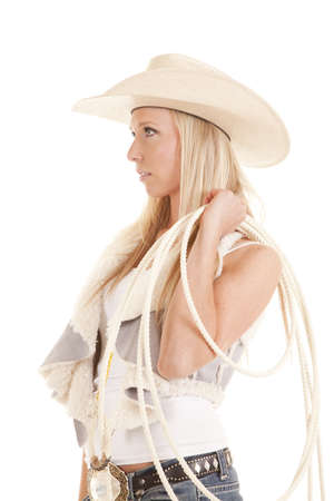 A cowgirl looking off to the side holding on to her rope.