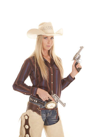 A cowgirl in her chaps holding on to her two pistols with a serious expression. photo