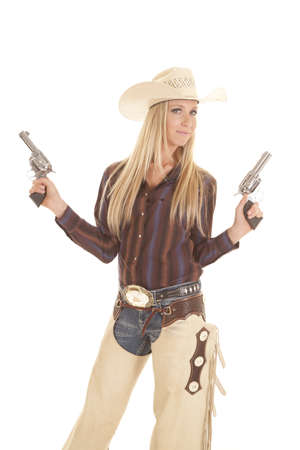 A cowgirl in her chaps holding on to her two pistols with a small smile on her face.  photo