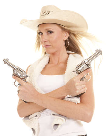 A cowgirl holding on to her two pistols acrossed her chest with a serious expression on her face with the wind blowing her hair. photo