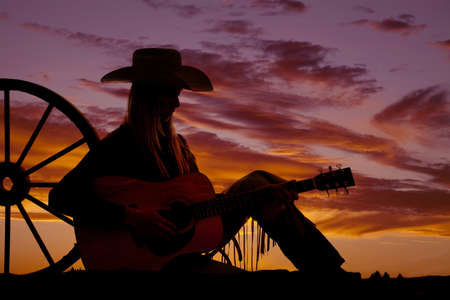 A cowgirl sitting up against a wagon wheel playing her guitar with the sunset behind her. photo