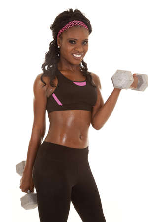 A woman working out with weights with a smile on her face. photo