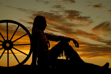 sitting on the ground: A woman sitting on the ground next to a wagon wheel with her chaps on.