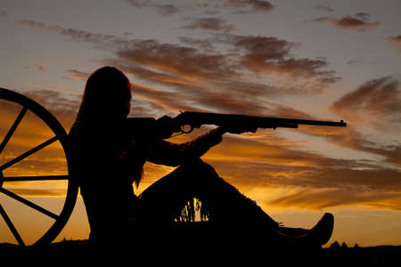 A woman sitting by a wagon wheel pointing her rifle . photo