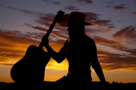 sexy cowgirl: A silhouette of a woman sitting down and holding on to her guitar. Stock Photo