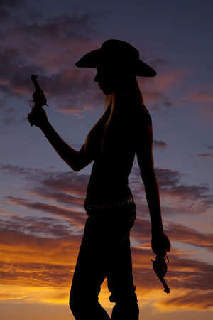 a silhouette of a woman standing holding two guns with a colorful sky behind her. photo