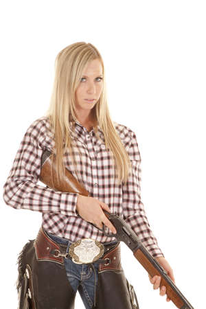 A cowgirl holding on to her rifle with  a serious expression on her face.