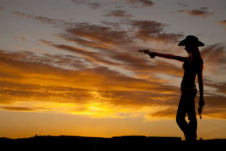 a silhouette of a cowgirl holding on to her guns pointing it at something Stock Photo