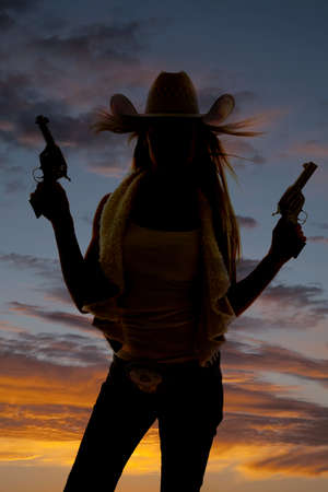 A silhouette of a cowgirl pointing her pistols up in the sky. photo