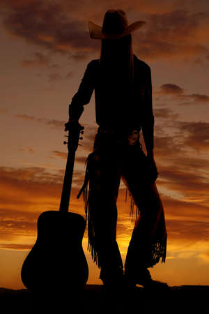 A cowgirl silhouette standing next to her guitar. photo