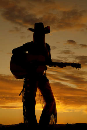 A silhouette of a cowgirl playing her guitar. photo