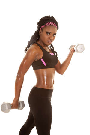 a woman working out with weights with a serious expression on her face. photo
