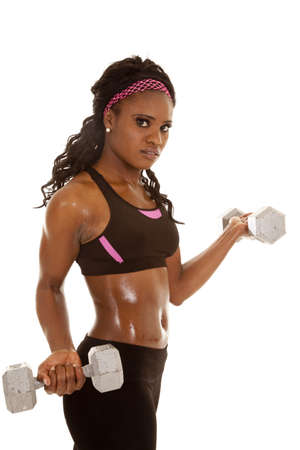 a woman working out with weights with a serious expression on her face 写真素材