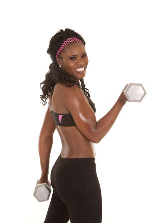 a woman doing an arm curl with a weight with a smile on her face. photo
