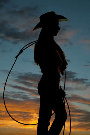 A silhouette of a cowgirl holding on to her rope.