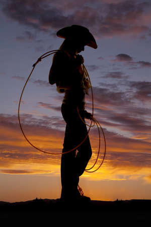 A silhouette of a woman looking down at the ground holdin on to her rope photo