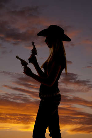 A silhouette of a woman holding on to her two pistols. photo